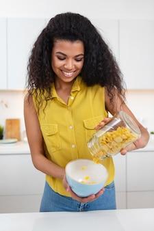 Kobieta przygotowuje miskę zbóż z mlekiem