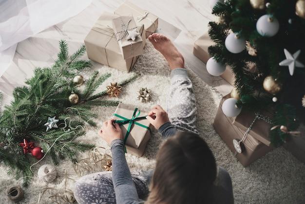 Kobieta przygotowuje prezent na podłodze