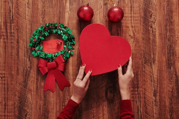 Kobieta przygotowuje prezent świąteczny w pudełku w kształcie serca z notatką i dużą kokardką dla swojego partnera