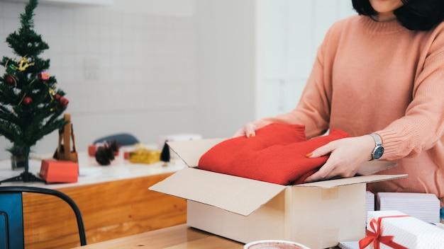 Kobieta przygotowuje prezenty na boże narodzenie i nowy rok.