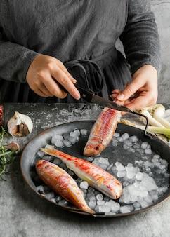 Kobieta przygotowuje rybę do gotowania