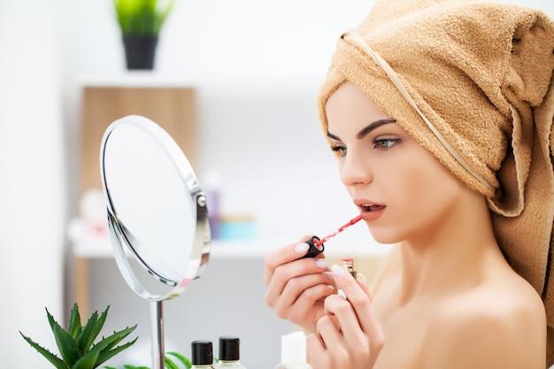 Kobieta przygotowuje się do pracy robi rano makijaż w łazience lustro w domu