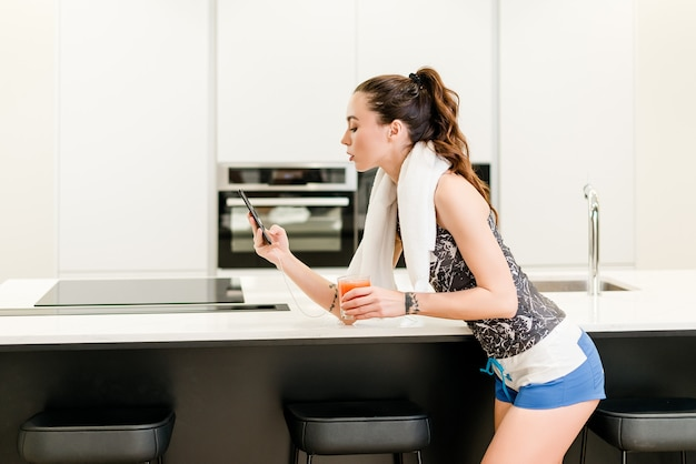 Kobieta przygotowuje się do treningu, picie soku i i patrząc na jej telefon