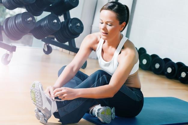 Kobieta przygotowuje się do treningu w siłowni