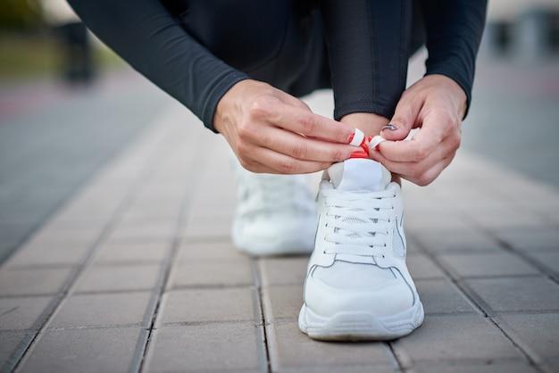 Kobieta przygotowuje się do uruchomienia. kobiece ręce wiązanie sznurowadeł na sportowe trampki