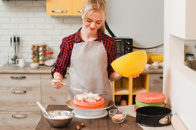 Kobieta przygotowuje słodkie domowe ciasto na drewnianym stole w kuchni