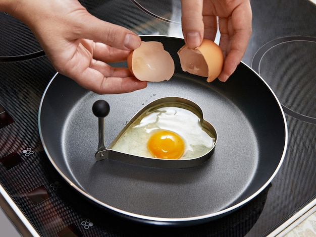 Kobieta przygotowuje smażone jajka w formie serca