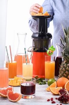 Kobieta przygotowuje soki cytrusowe z pomarańczy, grejpfruta, granatu, ananasa, mango na sokowirówce.