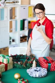 Kobieta przygotowuje świąteczne dekoracje i trzyma piłkę cacko