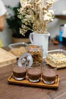 Kobieta przygotowuje w kuchni budyń chia, układając dolną warstwę mleka migdałowego, kakao i nasion chia.