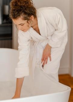 Kobieta przygotowuje wannę do kąpieli