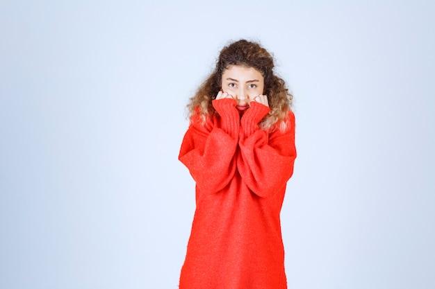 Kobieta przykłada pięści do podbródka i słucha uważnie z podnieceniem.