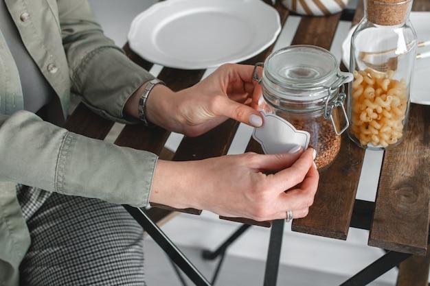 Kobieta przykleja naklejkę z napisem na słoiku z płatkami.