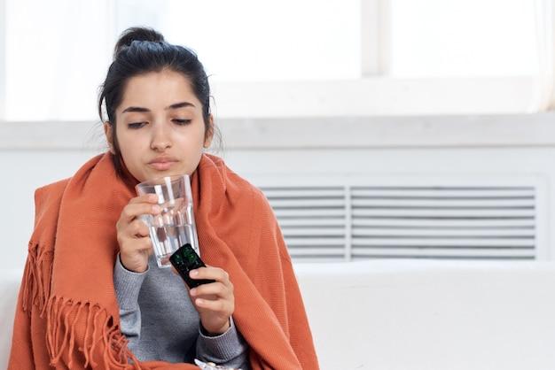 Kobieta przykrywająca szkocką kratę w domu szklanka na leki z wodą