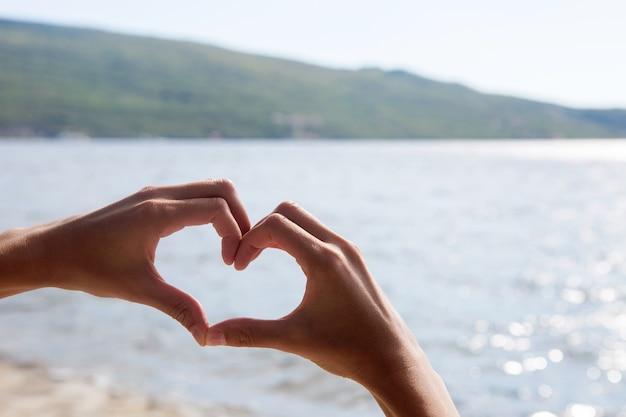 Kobieta przyłożyła ręce w kształcie serca do morza