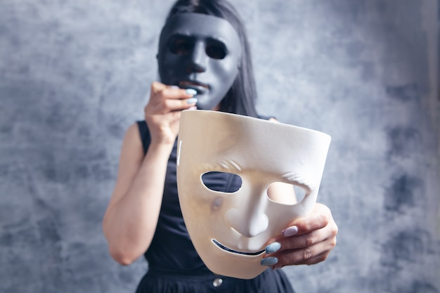Kobieta przymierza biało-czarną plastikową maskę