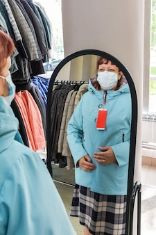 Kobieta przymierza jesienną kurtkę przed lustrem w sklepie odzieżowym z maską na twarzy