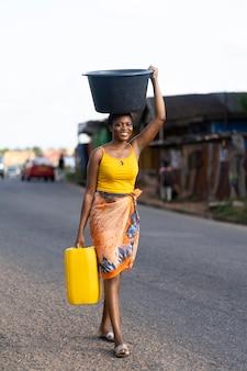Kobieta przynosząca wodę z zewnątrz
