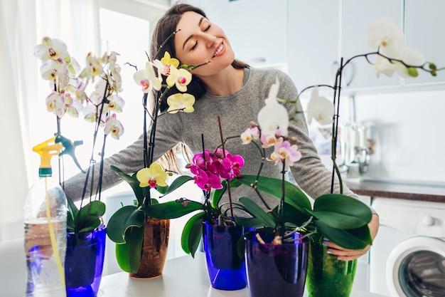 Kobieta przytula orchidee w kuchni. szczęśliwa gospodyni domowa dbająca o rośliny domowe i kwiaty.