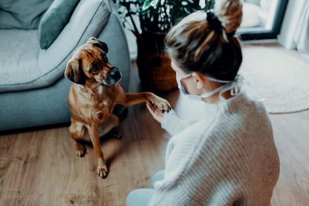 Kobieta przytula się bawi się ze swoim psem w domu z powodu pandemii koronawirusa covid19