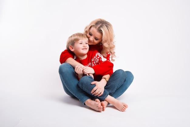 Kobieta przytula swoje dziecko i oboje siedzą na ziemi przy białej ścianie