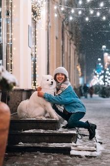 Kobieta przytula swojego psa na ulicy w nocy