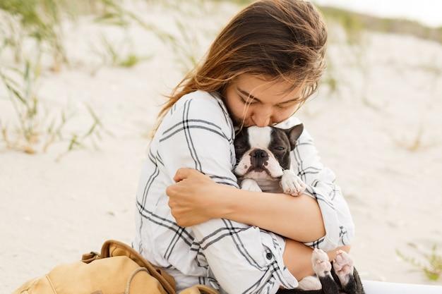 Kobieta przytulanie jej buldoga na plaży w świetle słońca, wakacje. stylowa dziewczyna z zabawnym psem odpoczywa, przytulanie i zabawy, urocze chwile.
