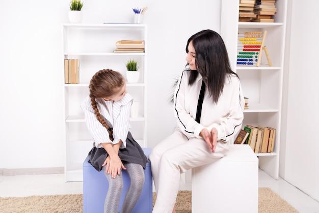 Kobieta psycholog doradza dziewczynce w gabinecie.