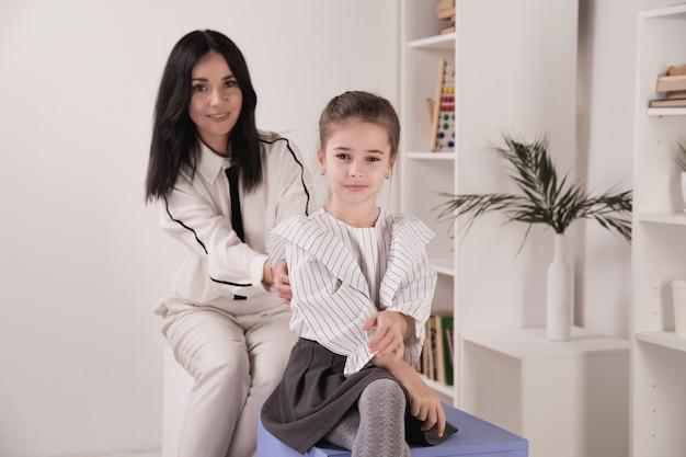 Kobieta psycholog pracuje z dziewczyną w białym gabinecie.