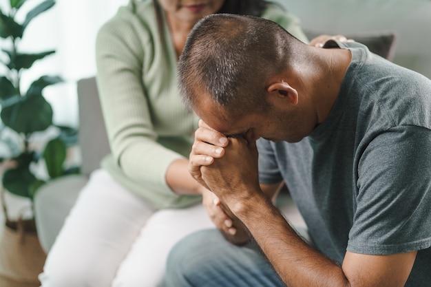 Kobieta psycholog, przyjaciółka lub rodzina siedzi i kładzie ręce na ramieniu, aby pocieszyć mężczyznę z depresją psychiczną, psycholog zapewnia pomoc psychiczną pacjentowi. pojęcie zdrowia psychicznego ptsd.
