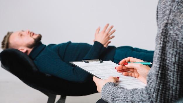 Kobieta psycholog z klientem wypełnia medyczną formę w sesji terapii