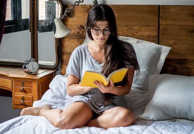 Kobieta r. w łóżku i czytanie książki