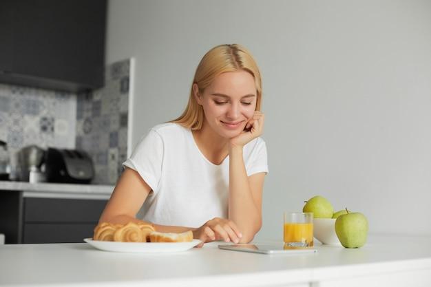 Kobieta rano siedzi przy kuchennym stole, uśmiechnięta, patrzy na czarny ekran tabletu i czyta wiadomość