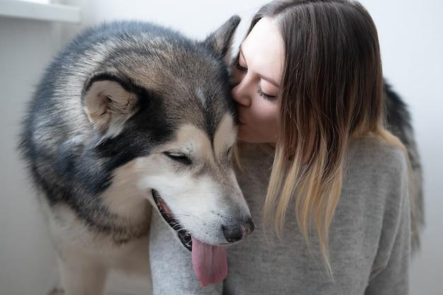 Kobieta rasy kaukaskiej całować psa alaskan malamute.