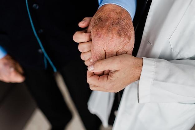 Kobieta rasy kaukaskiej czule trzyma pomarszczoną dłoń starszego mężczyzny.