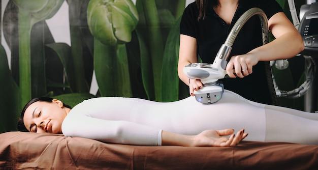 Kobieta rasy kaukaskiej leżącej na kanapie w centrum spa po procedurze lpg na jej specjalnym białym garniturze