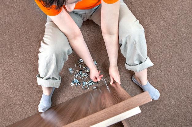 Kobieta rasy kaukaskiej montuje meble w domu za pomocą klucza imbusowego.