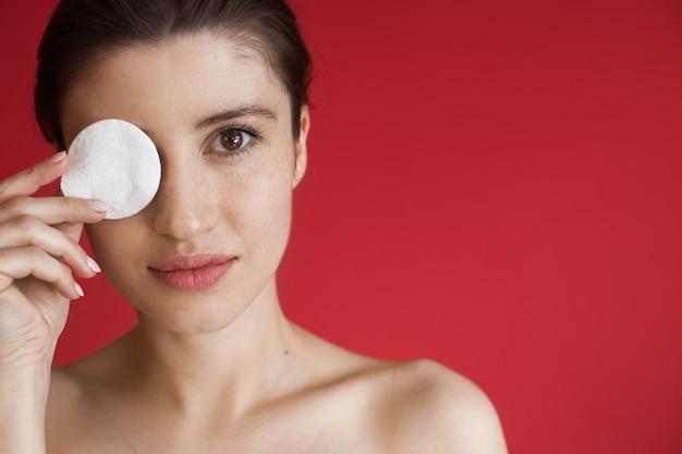 Kobieta rasy kaukaskiej reklamuje coś na czerwonej ścianie z wolną przestrzenią, zasłaniając oko podkładką i pozując z odkrytymi ramionami