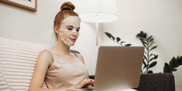 Kobieta rasy kaukaskiej, ubrana w specjalną maskę przeciwstarzeniową na twarz, siedząca na kanapie i pracująca z komputerem