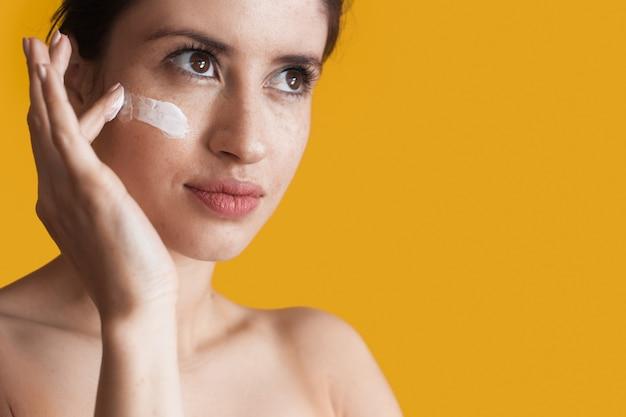 Kobieta rasy kaukaskiej z piegami nakłada na twarz krem przeciwzmarszczkowy