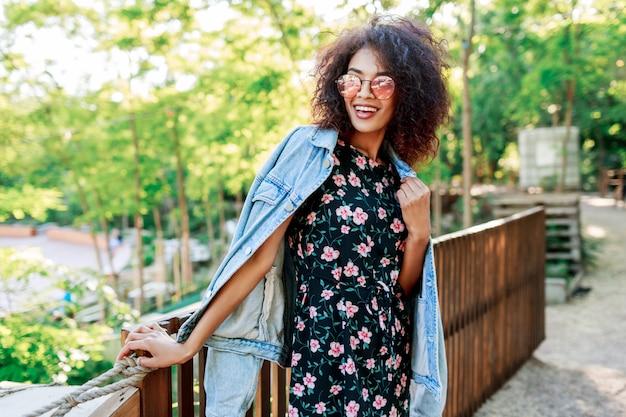 Kobieta rasy mieszanej o doskonałych zębach i włosach spędzająca wolny czas w parku
