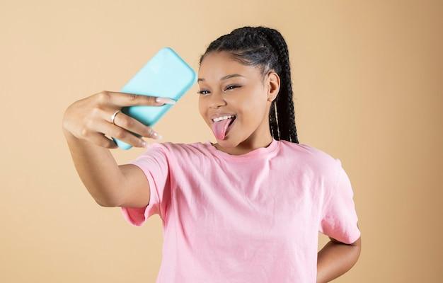 Kobieta rasy mieszanej robi selfie ze smartfonem wystającym jej język na żółtym tle