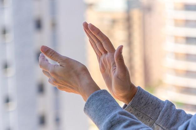 Kobieta ręce brawo, klaszcząc w ręce na balkonie