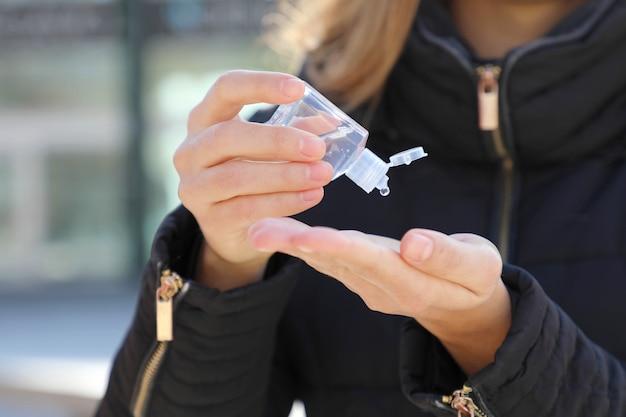 Kobieta ręce covid-19 używająca dozownika żelu do mycia rąk, przeciwko nowemu koronawirusowi (2019-ncov)