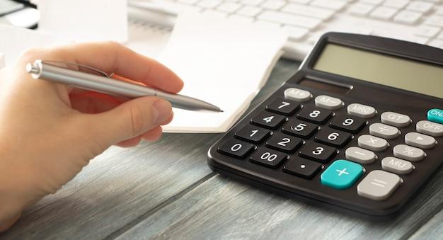 Kobieta ręce do pracy na kalkulatorze z bliska