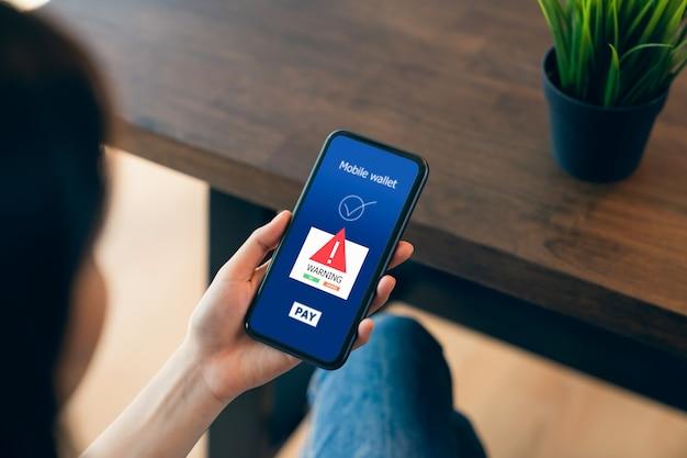 Kobieta ręce korzysta z telefonu i loguje się do bankowości mobilnej online z ekranem ostrzegawczym przed niebezpieczeństwem złośliwego oprogramowania.