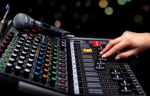 Kobieta ręce miksowania dźwięku przez analogowy mikser dźwięku
