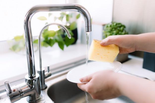Kobieta ręce mycia biały talerz z gąbką i mydłem w kuchni w zlewie pod bieżącą wodą.