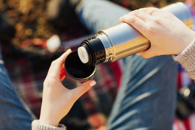 Kobieta ręce nalewanie gorącego napoju w kubek z termosu
