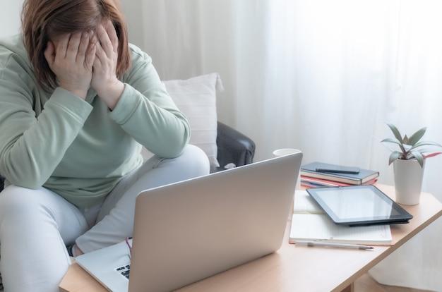 Kobieta ręce nogi freelancer stół sofa laptop pc domu pracy złe wieści zdenerwowany